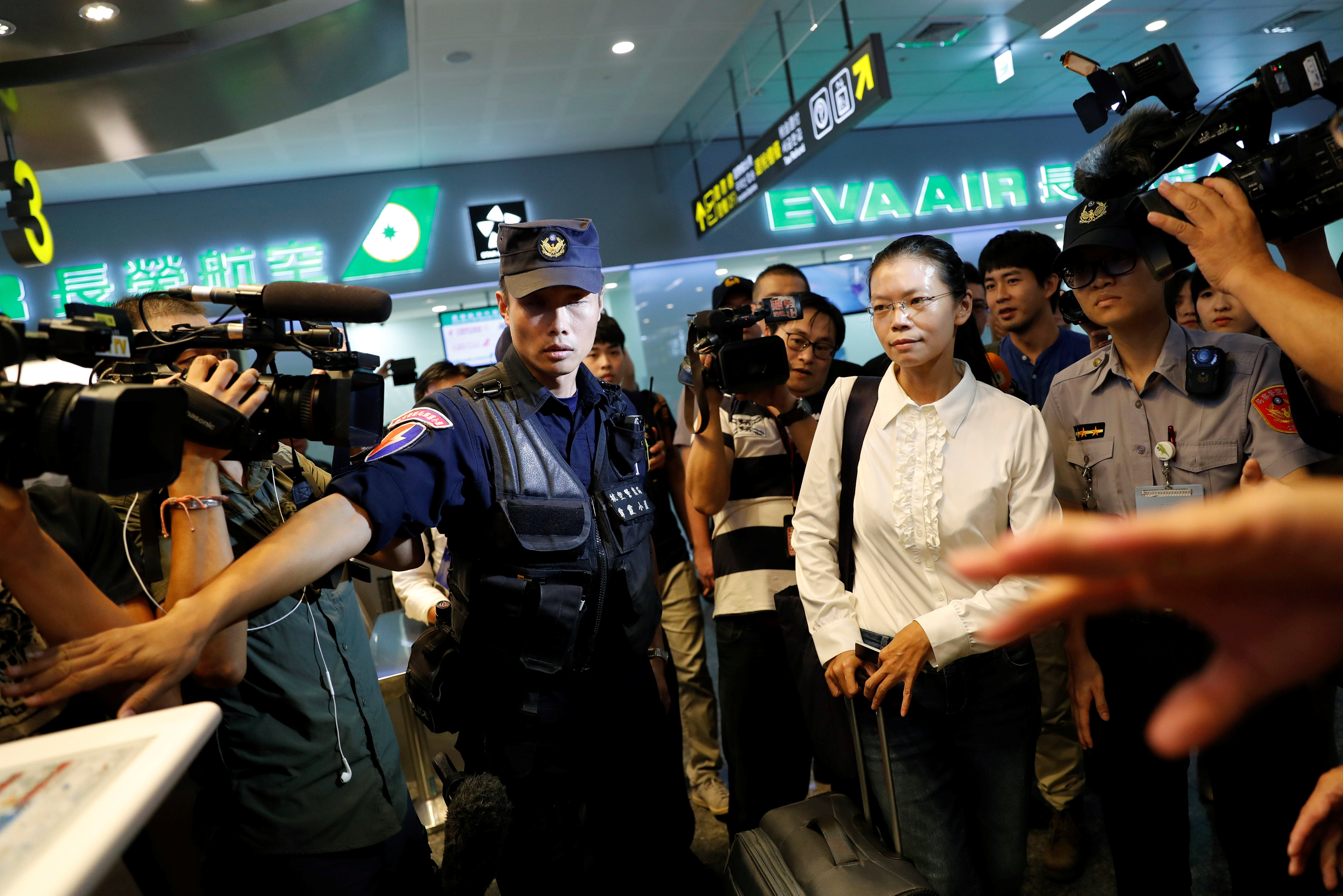 Lee Ching-yu, wife of Taiwan human rights advocate Lee Ming-che, also known as Li Ming-Che, who has been detained in China, departs for her husband's trial from the airport in Taipei, Taiwan on Sept. 10, 2017. (REUTERS/Tyrone Siu)