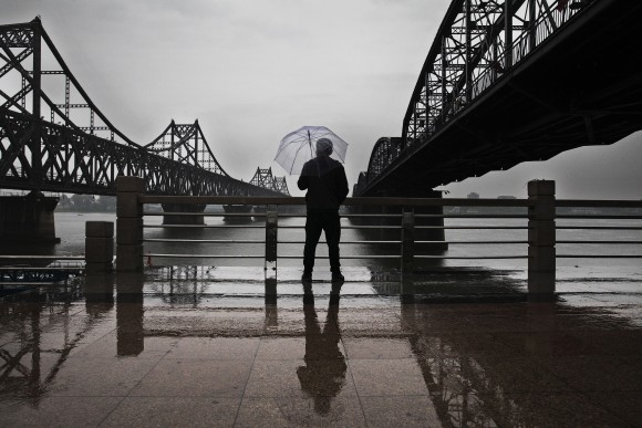 A Chinese man looks acrross the Yalu river at North Korean city of Sinuiju between the Friendship Bridge (L) and the Broken Bridge that connects the two countires in from Dandong, China, on May 23, 2017. (Kevin Frayer/Getty Images)