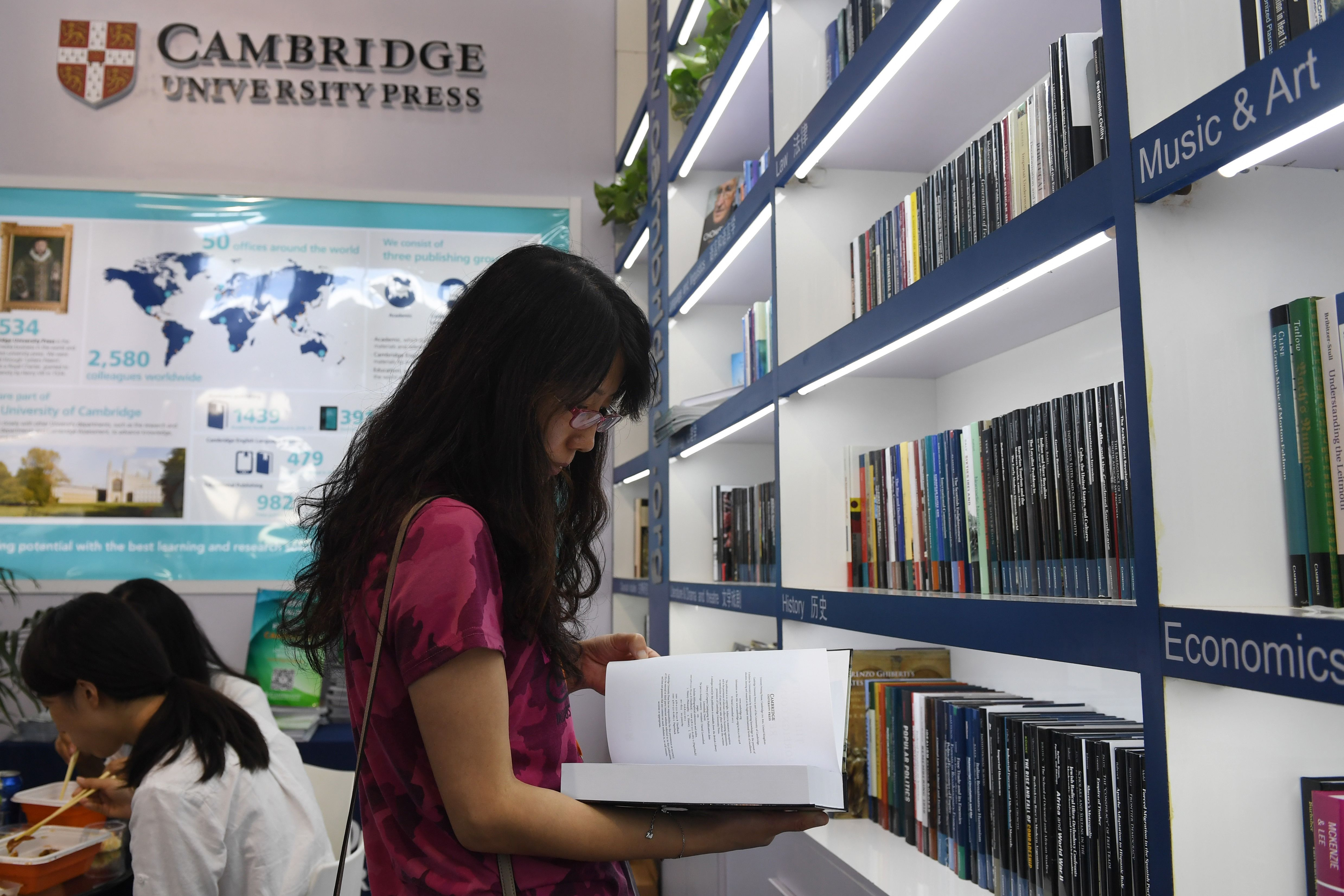 This photo taken on August 23, 2017 shows a woman reading a book at the Cambridge University Press stand at the Beijing International Book Fair in Beijing. (GREG BAKER/AFP/Getty Images)