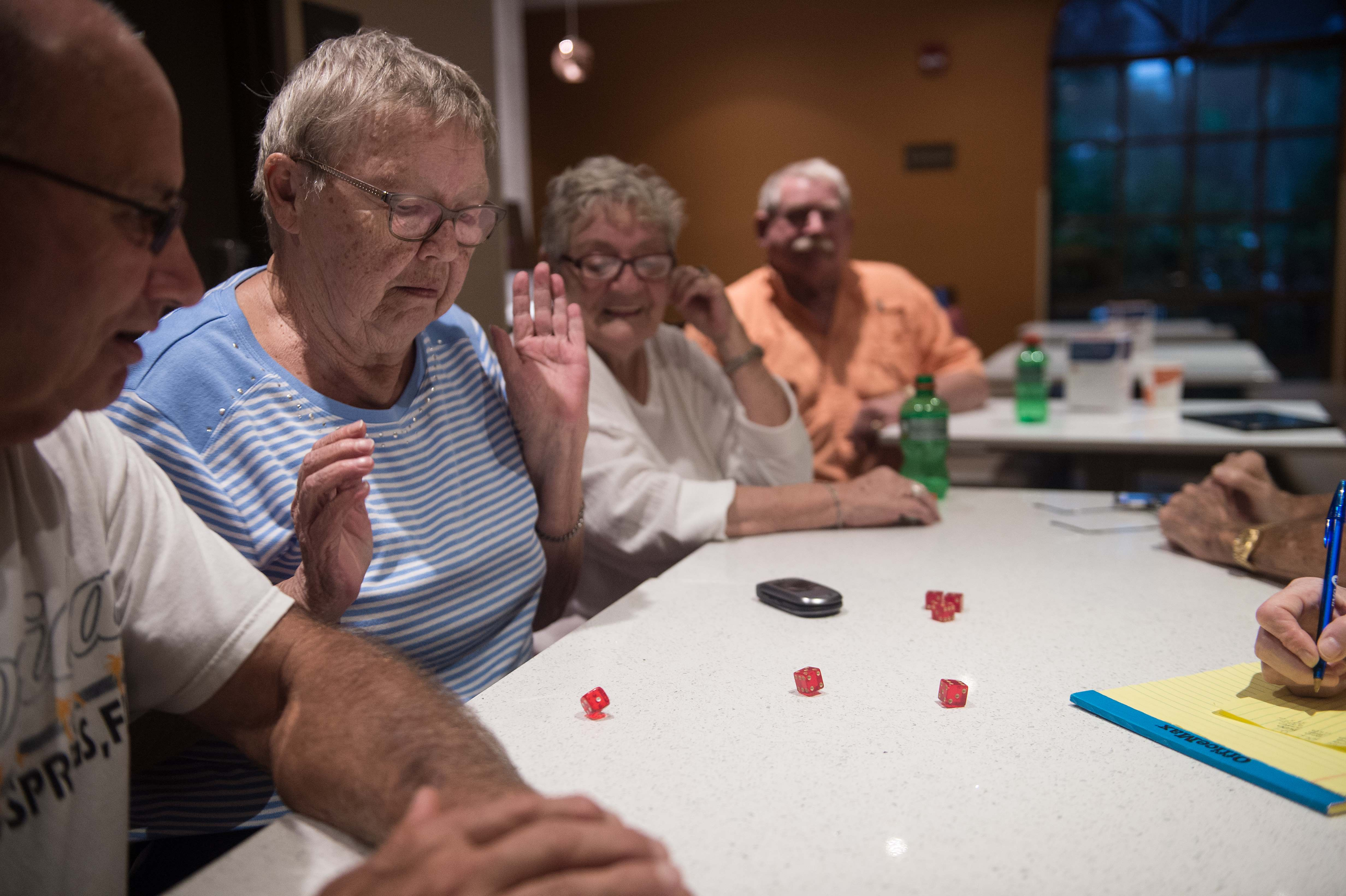 Retirees from nearby a mobile home community play dice in a hotel where they sought shelter in Bonita Springs, Florida as Hurricane Irma begins to hit Florida on Sept. 9, 2017. (NICHOLAS KAMM/AFP/Getty Images)