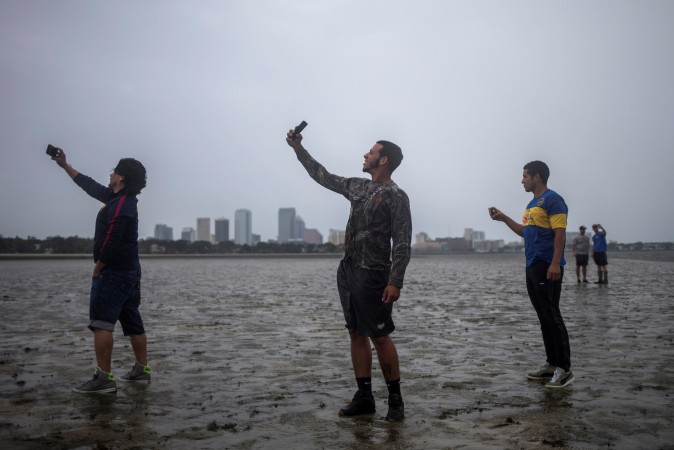 The Tampa skyline is seen in the background as local residents (L-R) Rony Ordonez, Jean Dejesus and Henry Gallego take photographs after walking into Hillsborough Bay ahead of Hurricane Irma in Tampa, Florida on Sept. 10, 2017. (REUTERS/Adrees Latif)