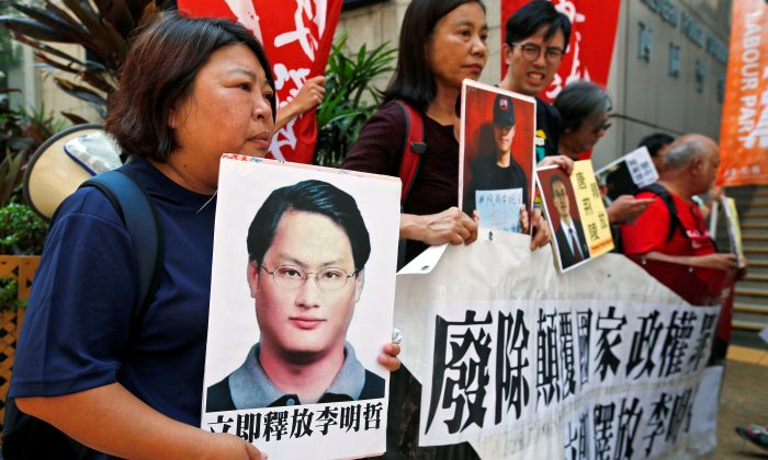 Pro-democracy protesters carry a photo of detained Taiwanese rights activist Lee Ming-Che (L) and other activists during a demonstration in Hong Kong, China on Sept. 11, 2017. (REUTERS/Bobby Yip)