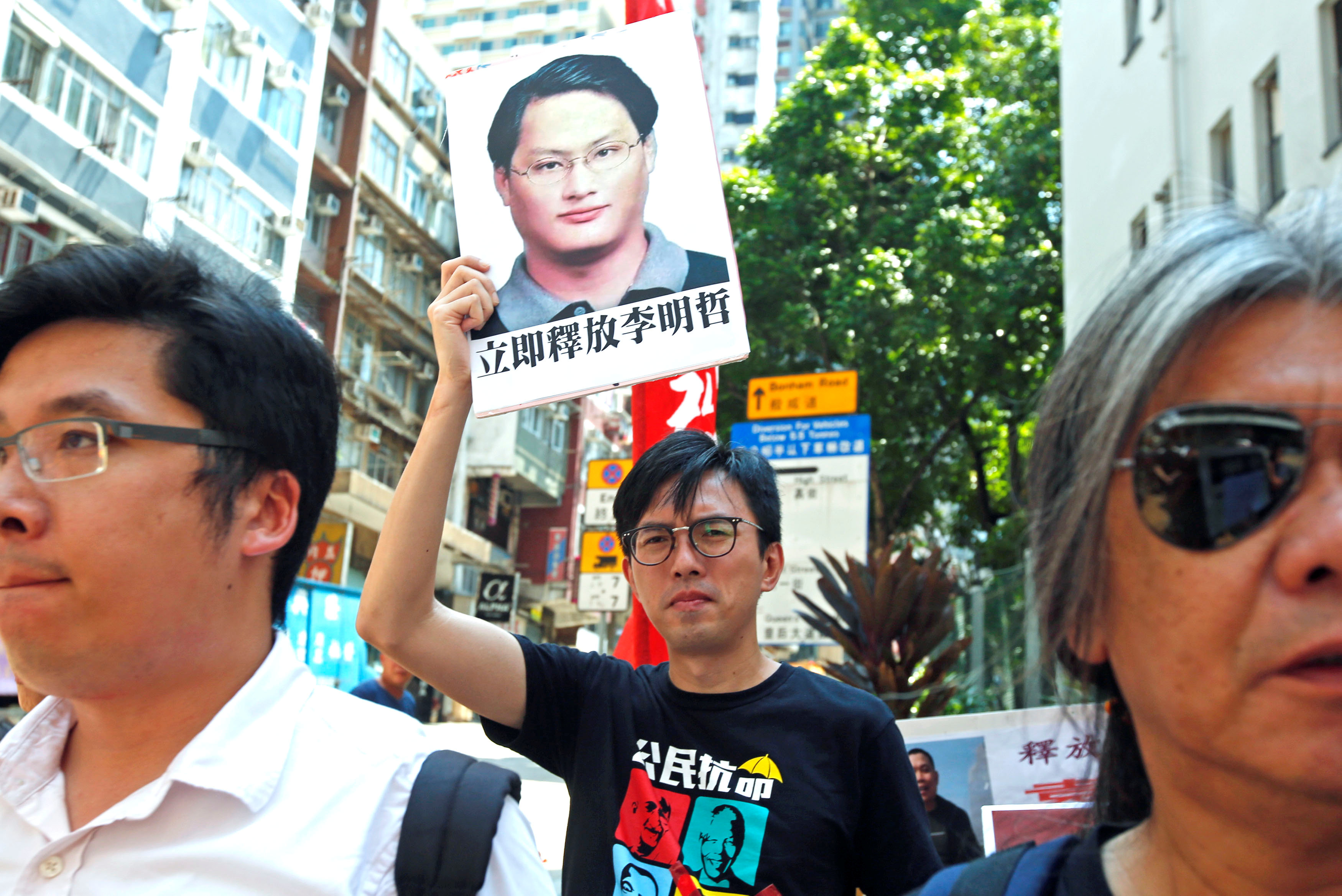 Pro-democracy protesters carry a photo of detained Taiwanese rights activist Lee Ming-Che during a demonstration in Hong Kong, China on Sept. 11, 2017. (REUTERS/Bobby Yip)