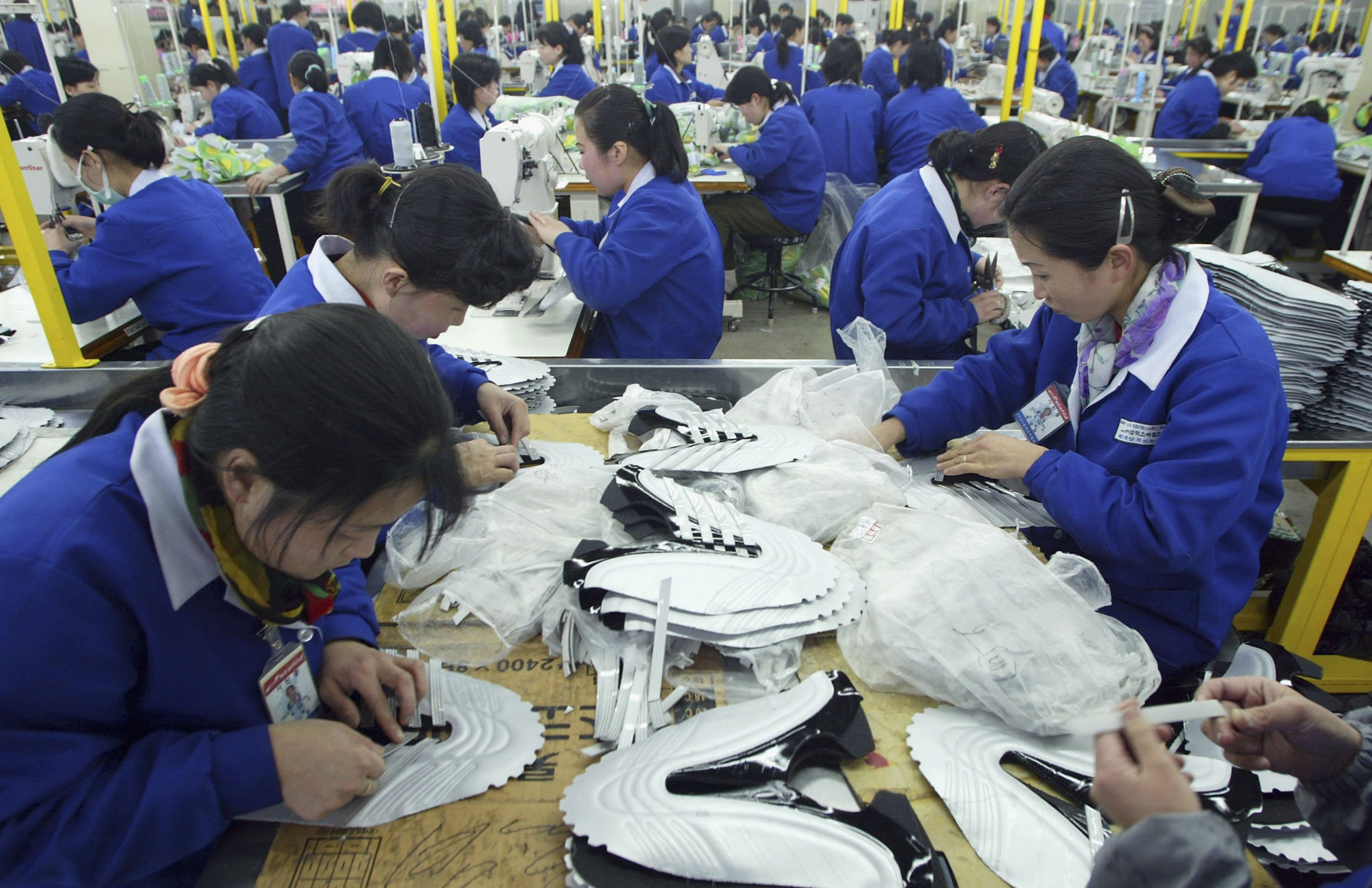 North Korean women work at the assembly line of the factory of shoemaker Samduk Inc. at the Kaesong industrial complex in Kaesong, North Korea on Feb. 27, 2006. (photo by Chung Sung-Jun/Getty Images)