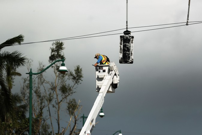 An electrical worker repairs stop lights the morning after Hurricane Irma swept through Naples, Florida on September 11, 2017. Utility companies in Florida have been warning customers of armed robbers posing as utility workers. Local police say reports of such robberies are fake news. (Spencer Platt/Getty Images)