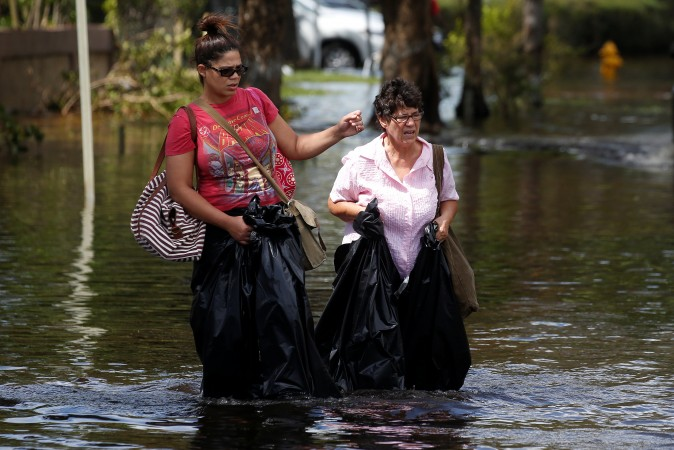 Women walk with garbage bags for waders on a flooded street following Hurricane Irma in North Miami, Florida, on Sept. 11, 2017. (Reuters/Carlo Allegri)