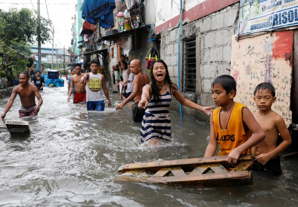 Residents wade in floodwaters in Quezon City, Metro Manila as a storm sweeps across the main Luzon island, Philippines, September 12, 2017. (Reuters/Dondi Tawatao)
