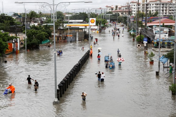 Residents wade and ride on pedicabs along a partially flooded road, in Las Pinas Metro Manila as a storm sweeps across the main Luzon island, Philippines, September 12, 2017. (Reuters/Erik De Castro)