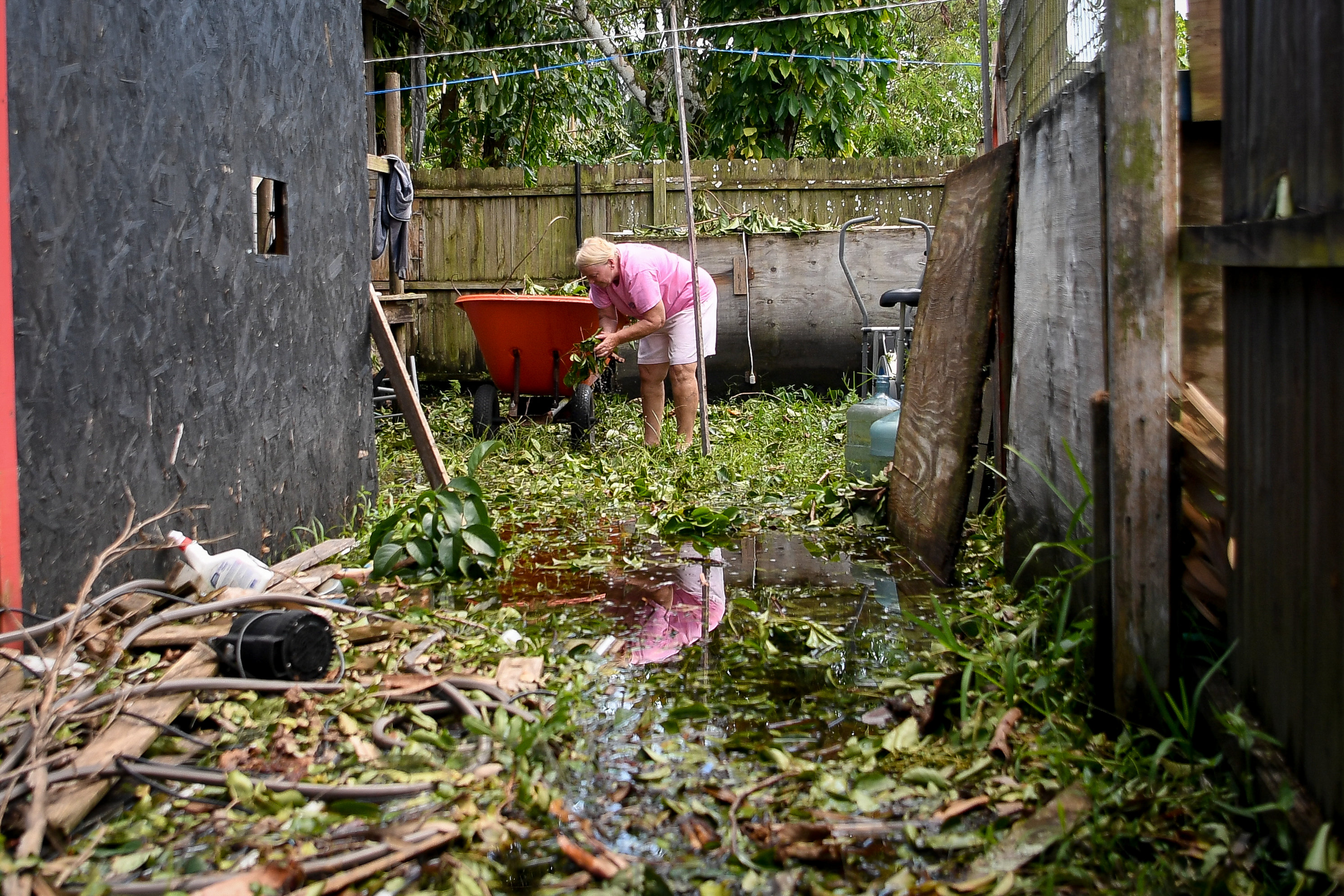 Joan Markel, stands in food waters cleaning debris from her yard, after Hurricane Irma near Jerome, Florida, U.S., September 12, 2017. (Reuters/Bryan Woolston)