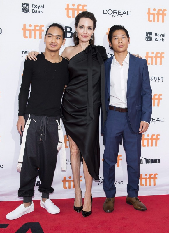 "(L-R) Maddox Jolie-Pitt, Angelina Jolie, and Pax Jolie-Pitt pose on the red carpet for the movie ""First They Killed My Father"" during the Toronto International Film Festival on Sept. 11, 2017. (THE CANADIAN PRESS/Nathan Denette)"