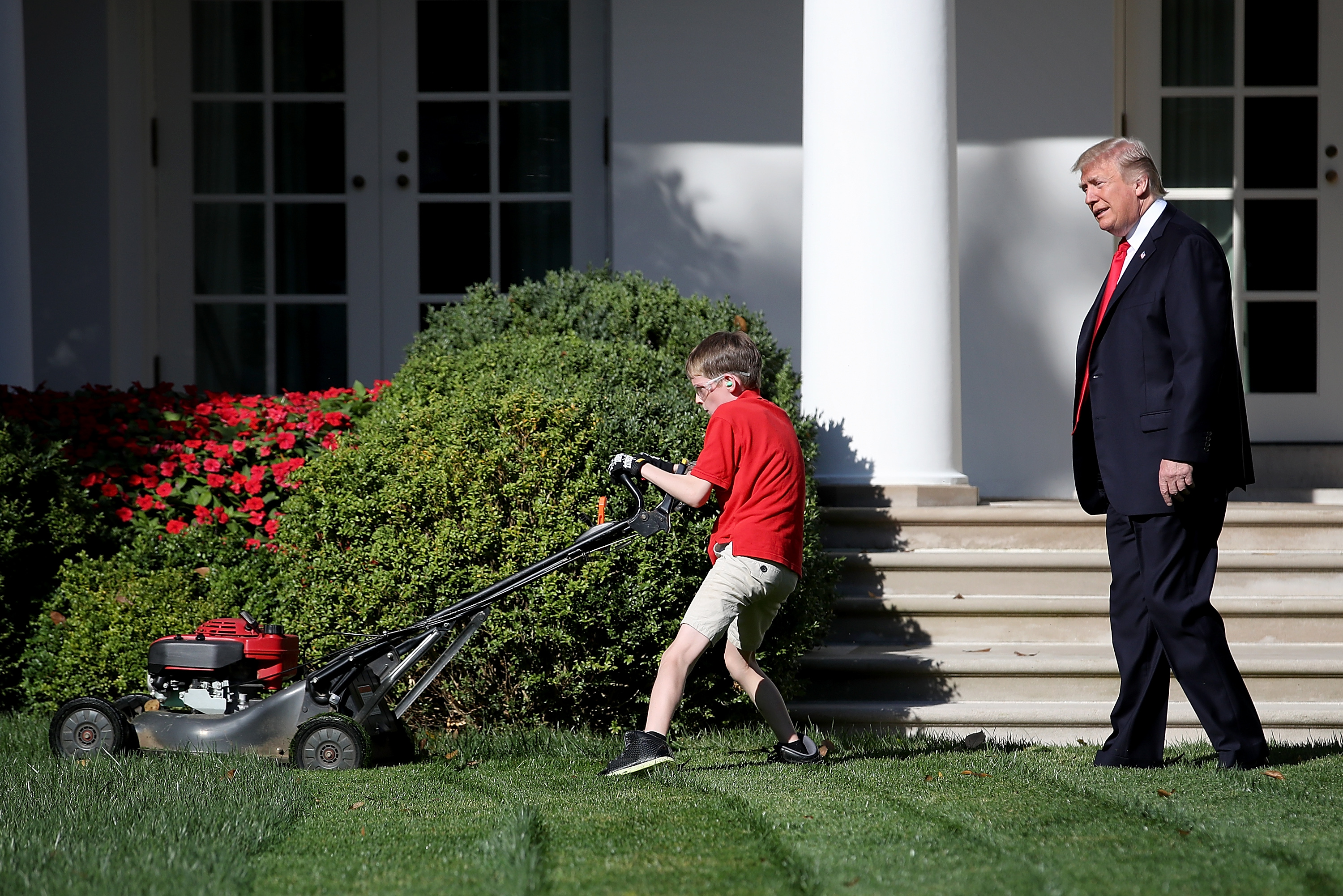 "WASHINGTON, DC - SEPTEMBER 15: U.S. President Donald Trump (R) watches as 11-year-old Frank ""FX"" Giaccio (L) mows the grass in the Rose Garden of the White House September 15, 2017 in Washington, DC. Giaccio, from Falls Church, Virginia, who runs a business called FX Mowing, wrote a letter to Trump expressing admiration for Trump's business background and offered to mow the White House grass. (Photo by Win McNamee/Getty Images)"