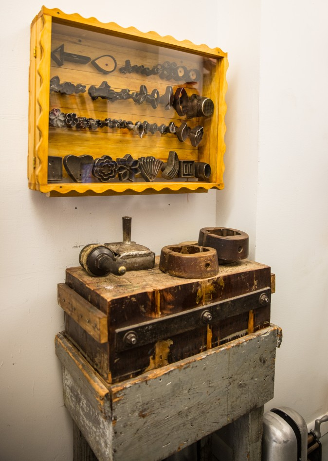 A collection of 100 year old cast iron millinery fabric molds in a case at the Jennifer Ouellette studio. (Benjamin Chasteen/The Epoch Times)