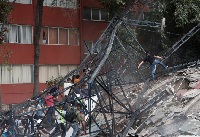 People climb over the debris of a collapsed building after an earthquake hit Mexico City, Mexico September 19, 2017. Picture taken September 19, 2017. (Reuters/Ginnette Riquelme)