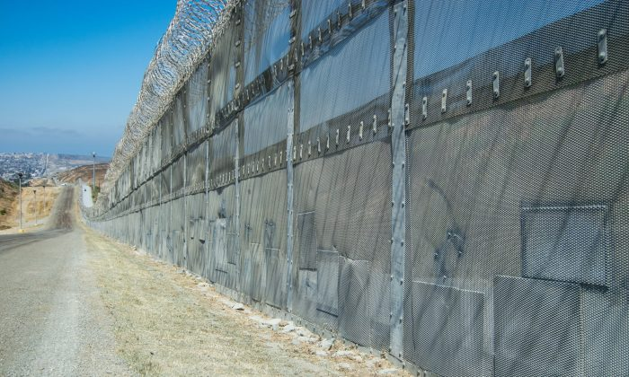 Patches line the bottom of the border barrier where illegal migrants cut through the fence, along the U.S.-Mexico border in San Diego on July 12, 2017. (Joshua PHilipp/The Epoch Times)