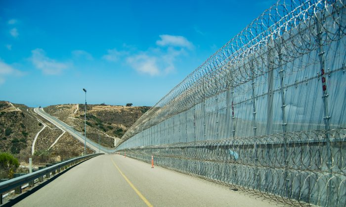 "The secondary fence of the U.S.–Mexico border near an area popularly known as ""Smuggler's Gulch"" in San Diego on July 12. The Border Patrol added a second layer of concertina wire along the bottom of the fence