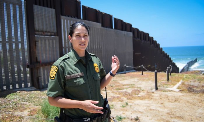 """San Diego Border Patrol agent Tekae Michael at the western end of the U.S.–Mexico border barrier in San Diego, Calif., on July 12, 2018. The """"PV-1"""" barrier is designed to stop both pedestrians and vehicles from illegally crossing the border. (Joshua Philipp/The Epoch Times)"""