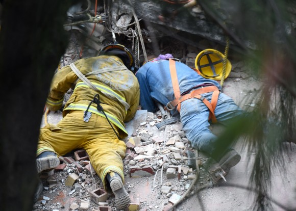 A firefighter and a rescuer search for survivors in Mexico City after a strong quake hit central Mexico on Sept. 20, 2017. (ESTRELLA/AFP/Getty Images)