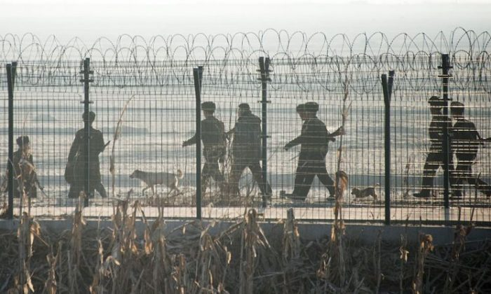 North Korean soldiers patrol next to the border fence near the town of Sinuiju across from the Chinese border town of Dandong on Feb. 10, 2016. (JOHANNES EISELE/AFP/Getty Images)