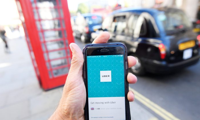 A photo illustration shows a London taxi passing as the Uber app logo is displayed on a mobile telephone, as it is held up for a posed photograph in central London on Sept. 22, 2017. (REUTERS/Toby Melville)