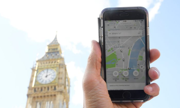 A photo illustration shows the Uber app on a mobile telephone, as it is held up for a posed photograph in central London, Britain on Sept. 22, 2017. (REUTERS/Toby Melville)