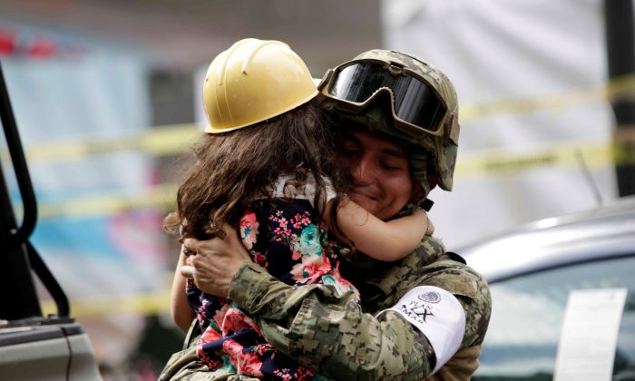 A girl hugs a Mexican marine officer as she offers hugs to people near the site of a collapsed building after an earthquake, in Mexico City, on Sept 25 2017. (REUTERS/Jose Luis Gonzalez)