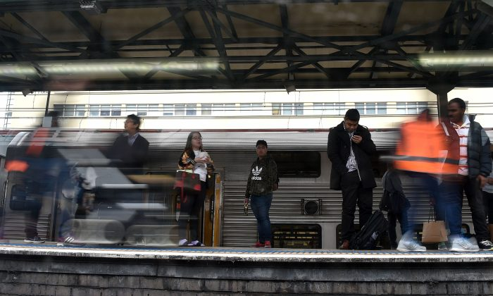 Passengers, seen through a train window, wait on the platform in the central business district of Sydney on April 11, 2017. (Saeed Khan/AFP/Getty Images)