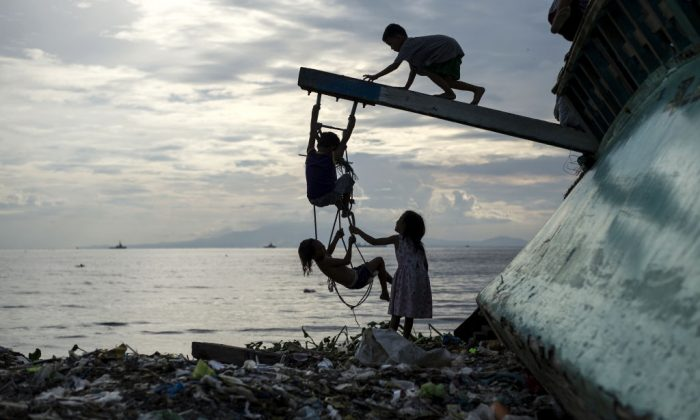 Filipino children play with a broken fishing boat in garbage filled Manila Bay. (Noel Celis/AFP/Getty Images)