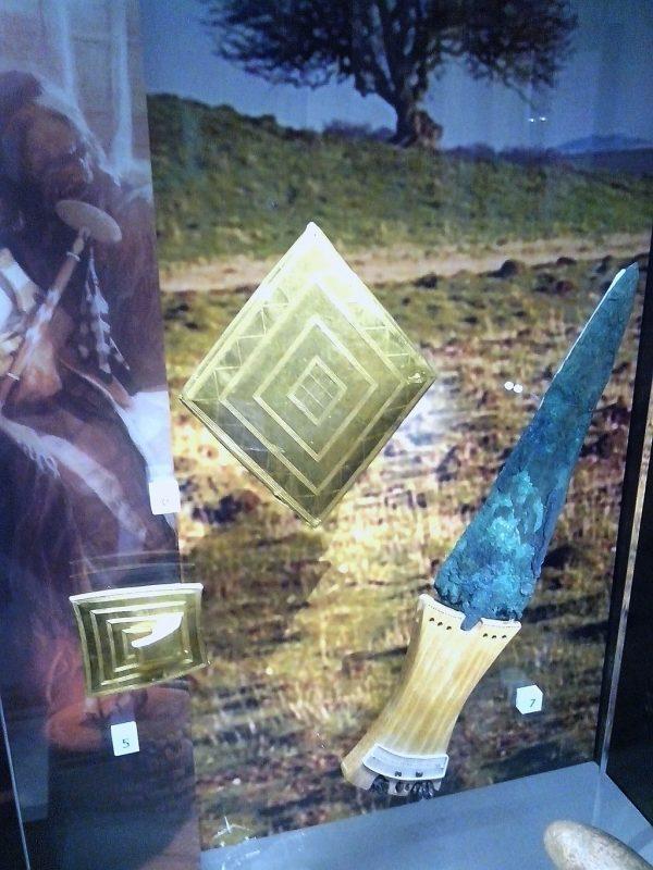 Gold lozenge, gold belt buckle, copper dagger. Bronze Age grave goods from Wilsford G5, Bush Barrow. Now in the Wiltshire Museum, Devizes. (Public Domain)