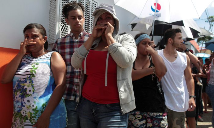People wait in line for aid items to be handed out in San Juan. (Reuters/Alvin Baez)