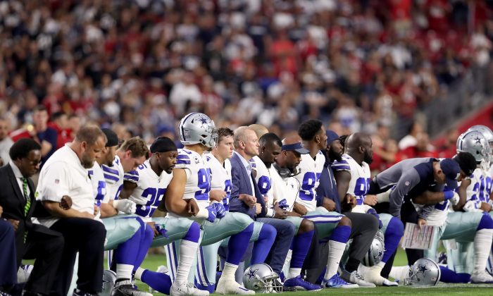 Members of the Dallas Cowboys take a knee before the start of the national anthem at an NFL game against the Arizona Cardinals at the University of Phoenix Stadium in Glendale, Ariz., on Sept. 25, 2017. (Christian Petersen/Getty Images)