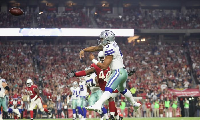 Quarterback Dak Prescott #4 of the Dallas Cowboys throws a pass under pressure from outside linebacker Markus Golden #44 of the Arizona Cardinals during the second half of the NFL game against the Arizona Cardinals at the University of Phoenix Stadium in Glendale, Arizona, on Sept. 25, 2017. (Christian Petersen/Getty Images)