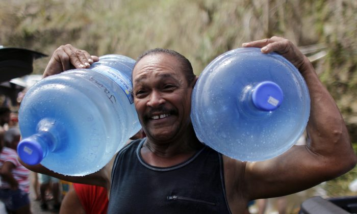 A man carries two water jugs filled with water collected from a natural spring created by the landslides in a mountain next to a road in Corozal, west of San Juan, Puerto Rico, on September 24, 2017 following the passage of Hurricane Maria.(Ricardo Arduengo/AFP/Getty Images)