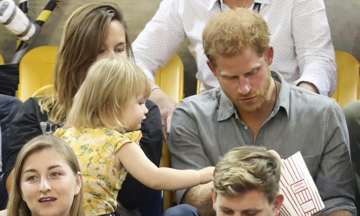 Prince Harry (R) sits with David Henson's wife Hayley Henson (L) and daughter Emily Henson at the Sitting Volleyball Finals during the Invictus Games 2017 at Mattamy Athletic Centre on Sept. 27, 2017, in Toronto.