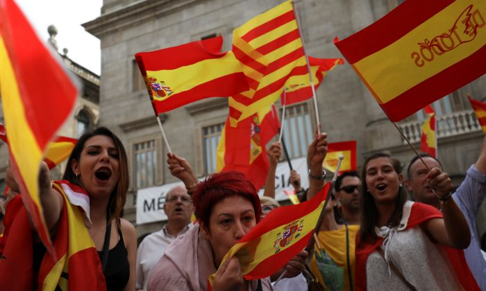 A woman kisses a Spanish flag as protesters hold Spanish and Catalan flags during a demonstration in favor of a unified Spain a day before the banned Oct. 1 independence referendum, in Barcelona, Spain, Sept. 30, 2017. (Susana Vera/Reuters)