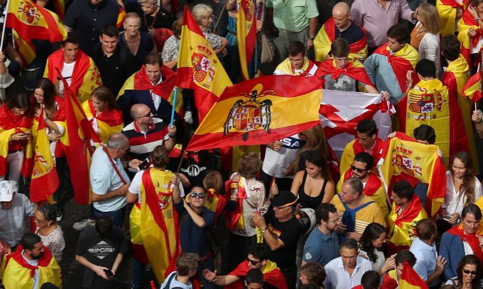 A demonstrator waves a pre-constitutional Spanish flag in front of city hall during a demonstration in favor of a unified Spain a day before the banned October 1 independence referendum, in Madrid, Spain, September 30, 2017. (Reuters/Sergio Perez)