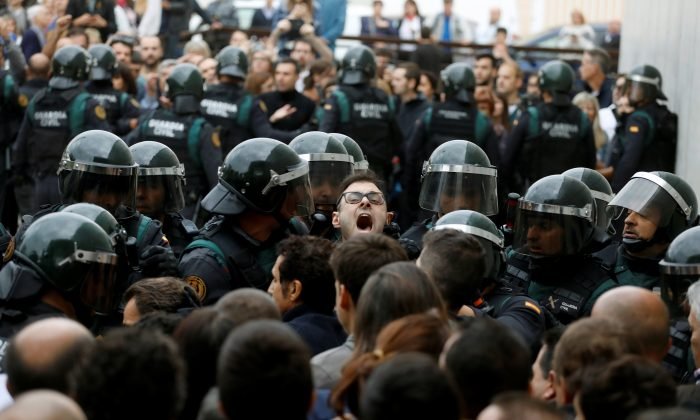 Scuffles break out as Spanish Civil Guard officers force their way through a crowd and into a polling station for the banned independence referendum where Catalan President Carles Puigdemont was supposed to vote in Sant Julia de Ramis, Spain on Oct. 1, 2017. (REUTERS/Juan Medina)