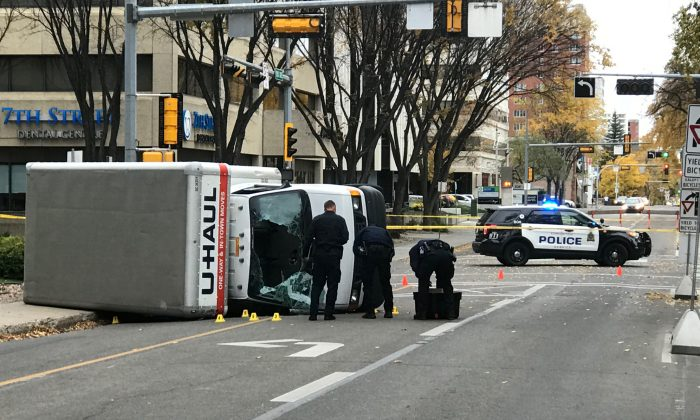 Edmonton Police investigate at the scene where a man hit pedestrians then flipped the U-Haul truck he was driving, pictured at the intersection at 107 Street and 100th Avenue in front of the Matrix Hotel in Edmonton, Alberta, Canada on Oct. 1, 2017.  (REUTERS/Candace Elliott)