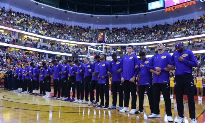 The Los Angeles Lakers lock arms during the national anthem before the start of the game against the Minnesota Timberwolves  at the Honda Center in Anaheim, Calif., on Sept. 30, 2017. (Robert Laberge/Getty Images)