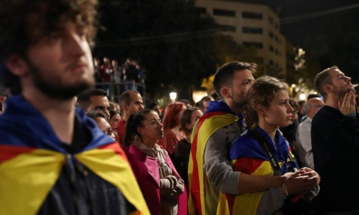 People react as they listen to Catalan president Carles Puigdemont during a gathering at Plaza Catalunya after voting ended for the banned independence referendum, in Barcelona, Spain on Oct. 1, 2017. (REUTERS/Susana Vera)