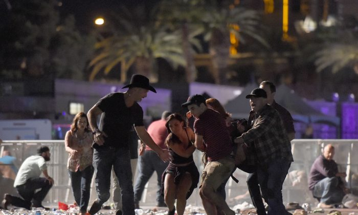 People carry a person at the Route 91 Harvest country music festival after a man opened fire on a crowd from the 32nd floor in Las Vegas, Nevada on Oct. 1, 2017. (David Becker/Getty Images)