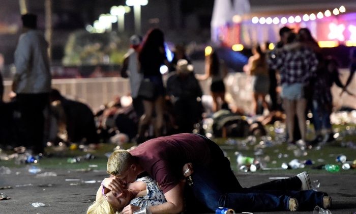 A man lays on top of a woman as others flee the Route 91 Harvest country music festival grounds after a active shooter was reported in Las Vegas on Oct. 1, 2017. A gunman opened fire on a music festival in Las Vegas, leaving at least 50 people dead. (Photo by David Becker/Getty Images)