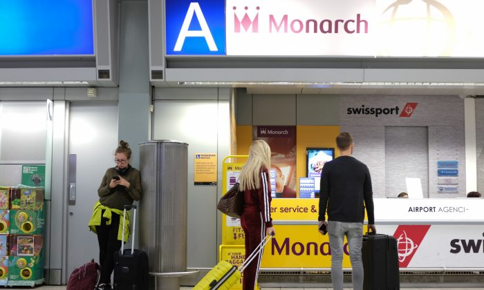 Passengers walk past the Monarch Airlines help desk at Luton Airport in England on Oct. 2, 2017. (Daniel Leal-Olivas/AFP/Getty Images)