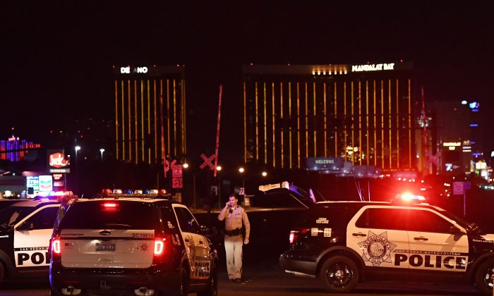 Police form a perimeter around the road leading to the Mandalay Hotel (background) after a gunman killed at least 50 people and wounded more than 200 others when he opened fire on a country music concert in Las Vegas, Nevada on Oct. 2, 2017.  (MARK RALSTON/AFP/Getty Images)