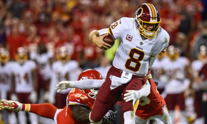 Quarterback Kirk Cousins No. 8 of the Washington Redskins tries to break the tackle attempt of defensive end Allen Bailey No. 97 and Jacoby Glenn No. 39 of the Kansas City Chiefs at Arrowhead Stadium on Oct. 2, 2017, in Kansas City, Mo. (Jason Hanna/Getty Images )