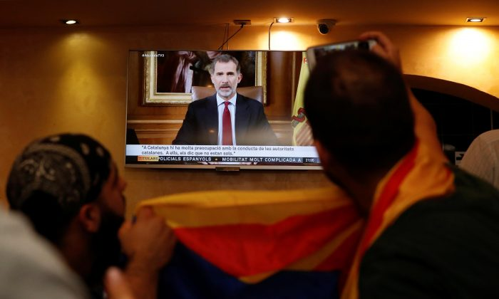 Patrons in a restaurant watch as Spanish King Felipe makes a televised address to the nation in Barcelona, Spain, Oct. 3, 2017.