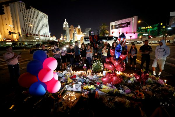 People gather at a makeshift memorial in the middle of Las Vegas Boulevard following the mass shooting in Las Vegas, Nevada on Oct. 4, 2017. (Reuters/Chris Wattie)