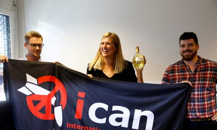 Beatrice Fihn, Executive Director of the International Campaign to Abolish Nuclear Weapons (ICAN) receives a bottle of champagne from her husband Will Fihm Ramsay (R) next to Daniel Hogsta, coordinator, while they celebrate after ICAN won the Nobel Peace Prize 2017, in Geneva, Switzerland on Oct. 6, 2017. (REUTERS/Denis Balibouse)