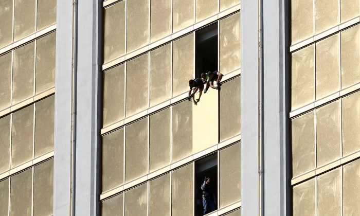 Workers board up a broken window at the Mandalay Bay hotel, where shooter Stephen Paddock conducted his mass shooting along the Las Vegas Strip, in Las Vegas, Nevada, U.S., October 6, 2017. REUTERS/Chris Wattie