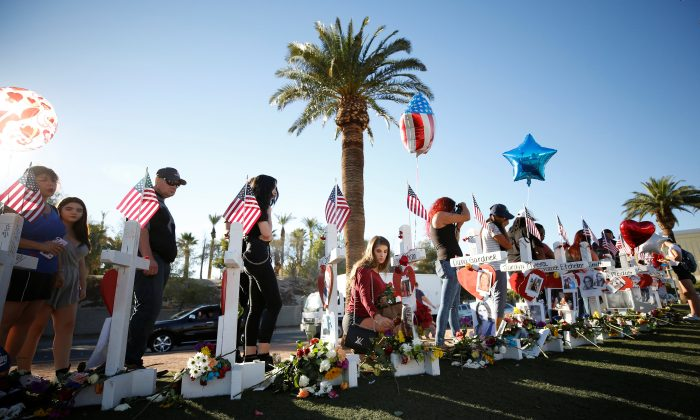 A woman places a flower in front of one of many white crosses set up for the victims of the Route 91 Harvest music festival mass shooting in Las Vegas, Nevada, U.S., October 6, 2017. (Reuters/Chris Wattie)