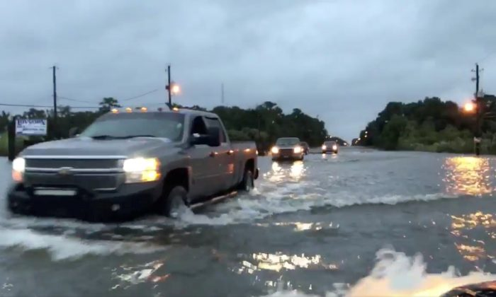 Cars drive through a flooded road in Mobile, Alabama on Oct. 8, 2017, in this still image taken from a video obtained from social media. (Michael Schubert/social media/via REUTERS)